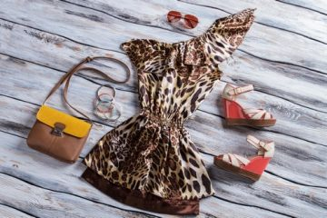 Leopard dress with bicolor purse. Aviator sunglasses and colorful bracelets. New items on showcase. Low prices for designer clothes.